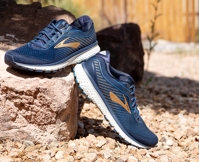 Brooks Ghost 12 running shoes placed on rocks outside.  Colors: Navy and Deep Water