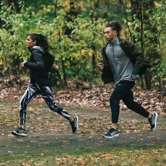 Woman and man, outfitted in Nike gear, running on an outdoors trail with fallen leaves around them.