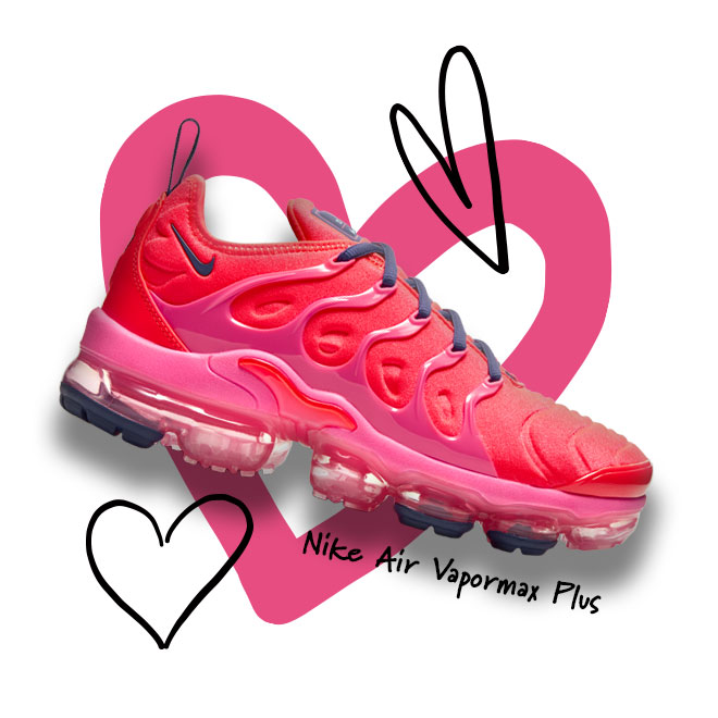 A Nike Air Vapormax Plus sneaker in the Bright Crimson/Pink Blast/Court Purple colorway with a heart outline in the background.