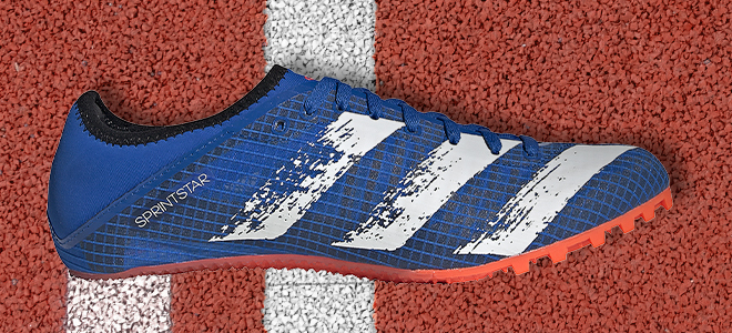 An adidas Sprintstar track spike in the glory blue/signal green/core black colorway lying on the track.