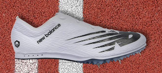A New Balance MD500 V7 track spike in the white/black colorway lying on the track.