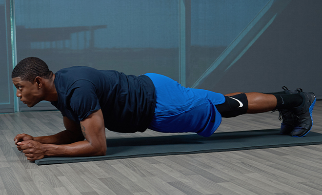 A man wearing does a plank on a yoga mat.